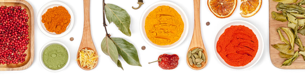 a selection of brightly coloured spices set against a white background